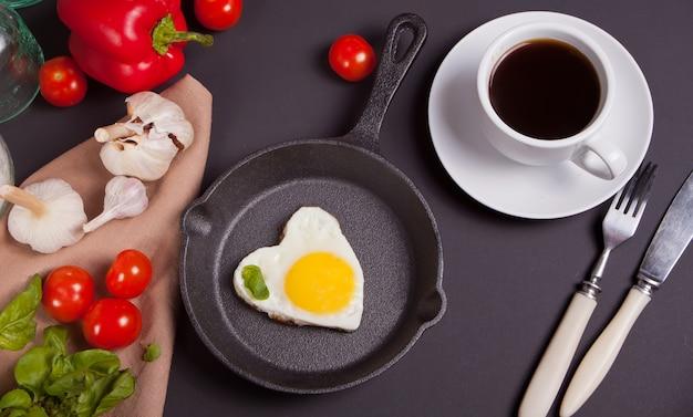 Heart shape scrambled eggs on iron dark pan