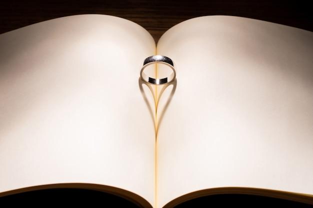 空の本バレンタインと愛の概念の毎日の真ん中にリングとハート形の影
