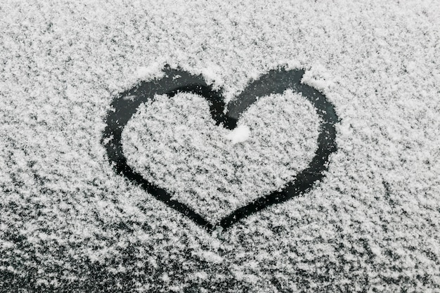 Heart shape on snowy glass during winter day