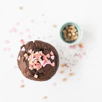 Heart shape sprinkles over cupcake on white background