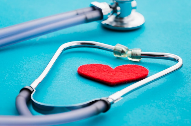Heart shape in the stethoscope on blue background