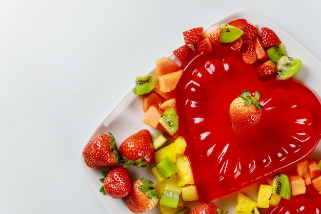 Heart shape strawberry gelatin decorated with fresh strawberry, kiwi and pineapple. dessert for couple.