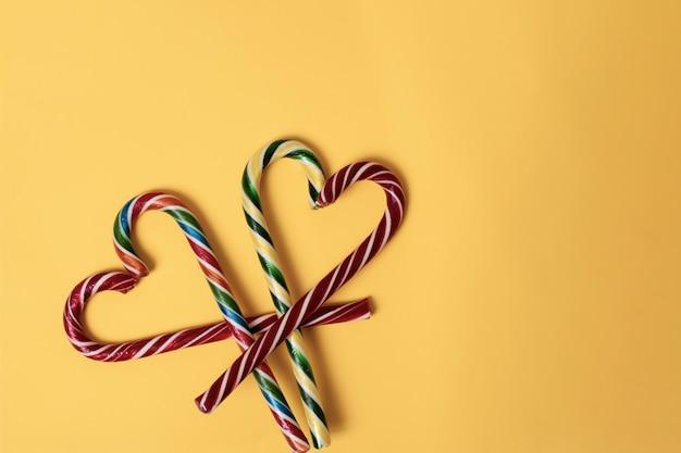 黄色の背景、上面図、コピースペース、ミニマリズムのクリスマスキャンディケインとハートの形