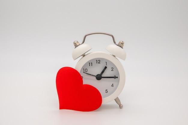 ハート型の目覚まし時計とハート。テキストの場所。上面図。愛と挨拶の時間。