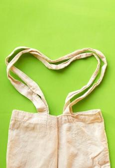 Сумка в форме сердца обрабатывает холст, ткань, ткань, эко-мешок для покупок, пустой шаблон на зеленом фоне. концепция защиты земли
