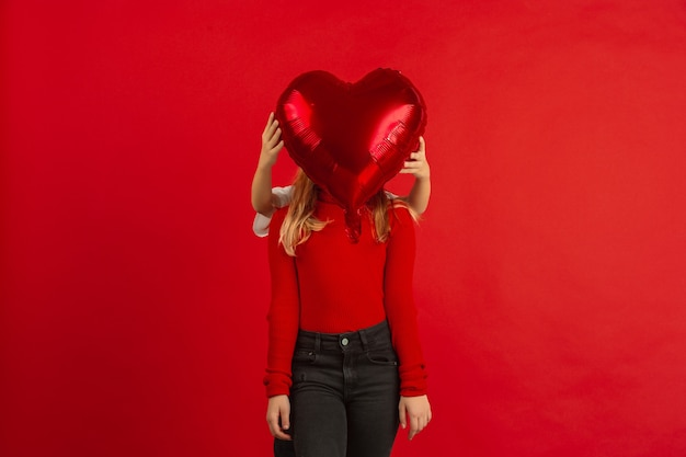 Heart-shaped balloon in front of a girl's face