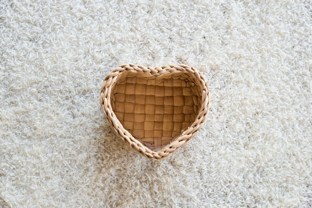 Heart-shaped basket on rice background