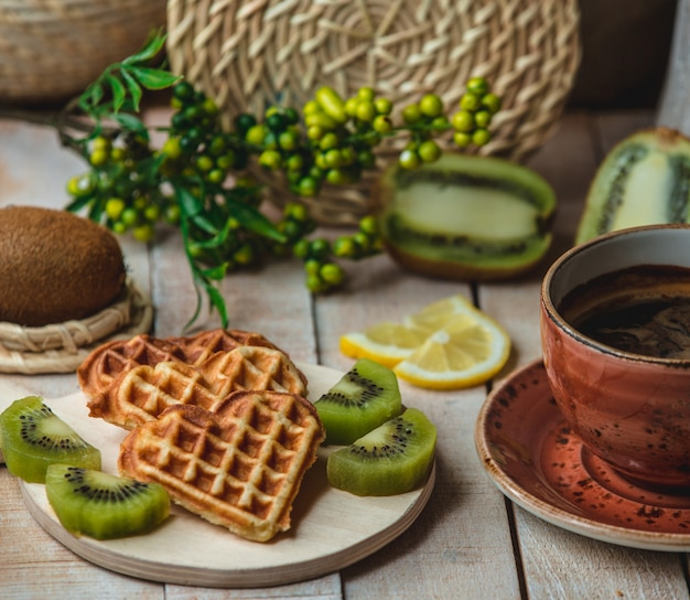 Heart shaped belgian waffles with kiwi slices and a cup of coffee