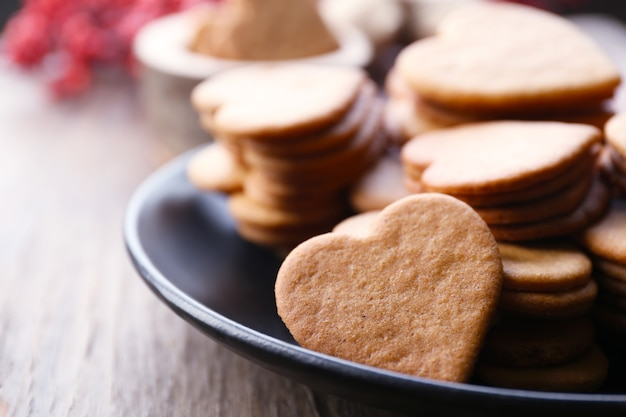 Heart shaped biscuits on plate with ash berry on wooden
