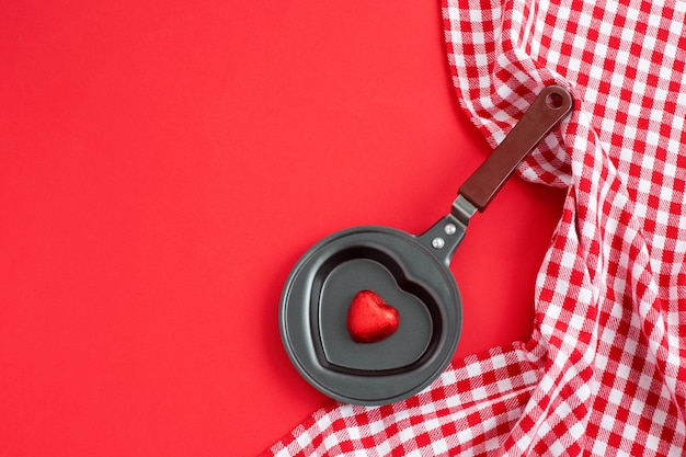 Heart shaped black metal egg frying pan with candy