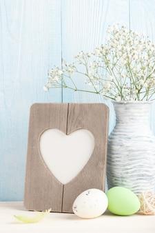 심장 모양의 빈 프레임, 부활절 달걀과 푸른 나무 배경에 흰색 꽃