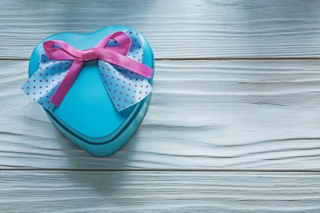 木の板の休日のコンセプトにピンクの弓とハート型の青いギフトボックス