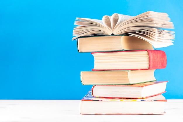 古いハードカバーの本のスタック上のハート形の本のページ。学校に戻る。教育