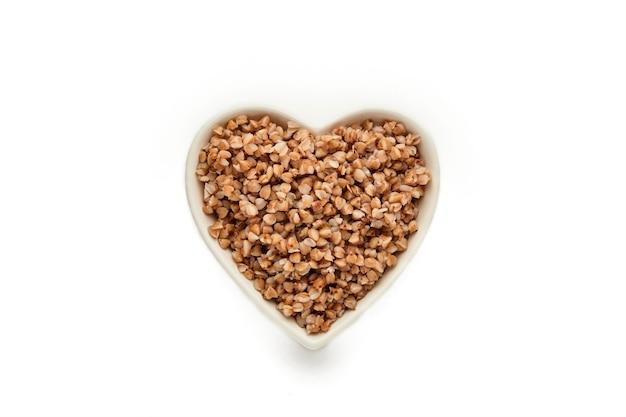 Heart-shaped bowl of boiled buckwheat porridge isolated in white