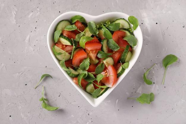 トマト、きゅうり、ルッコラ、大根のマイクログリーンと灰色のコンクリートの背景、健康的な食事の日、上面図と健康的なサラダとハート型のボウル
