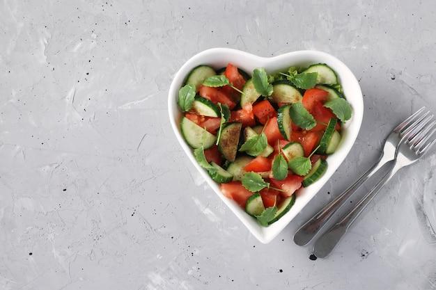 Миска в форме сердца с салатом из помидоров, огурцов, рукколой и микрозеленью редиса на сером бетонном столе