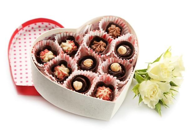 사탕과 꽃이 있는 하트 모양의 상자를 닫습니다.