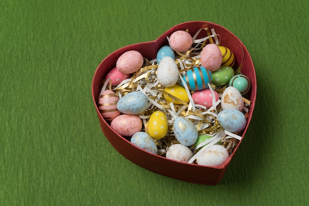 Heart shaped box with colorful easter eggs. festive eggs on green background. happy easter.