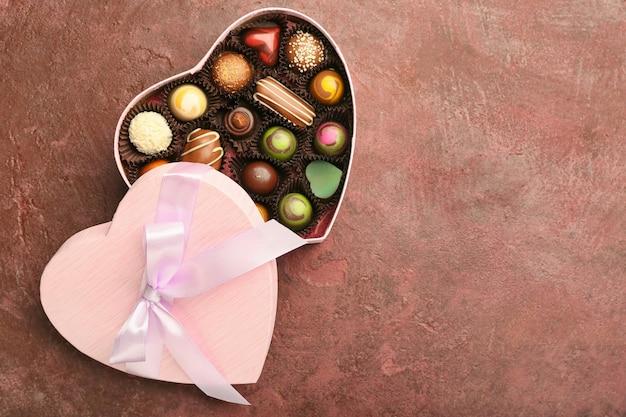 색상 표면에 맛있는 사탕이있는 하트 모양 상자
