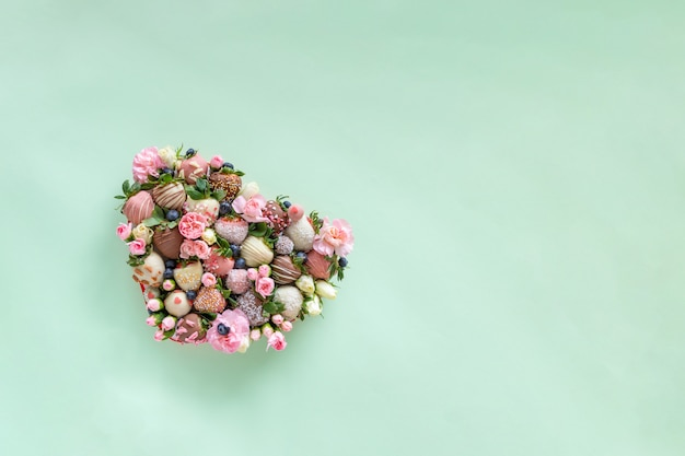 Heart shaped box with handmade chocolate covered strawberries with different toppings and flowers as a present on valentines day on green background with free space for text
