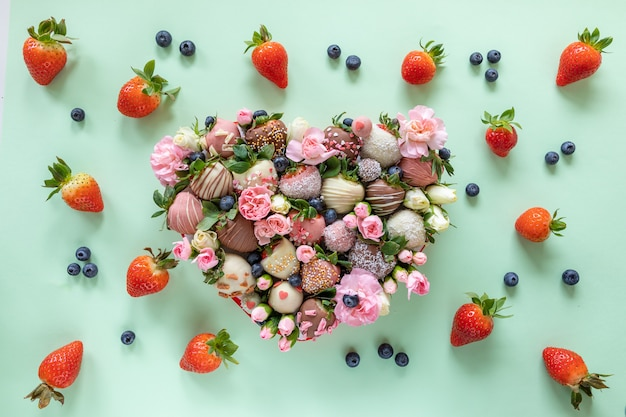Heart shaped box with handmade chocolate covered strawberries with different toppings and flowers as a present on valentines day on green background