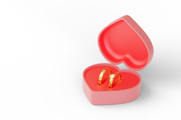 Heart shaped box with two wedding rings isolated on white background.