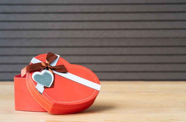 Heart-shaped box on wood background