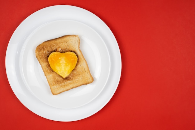Heart shaped breakfast sandwich with egg in the middle on a plate.