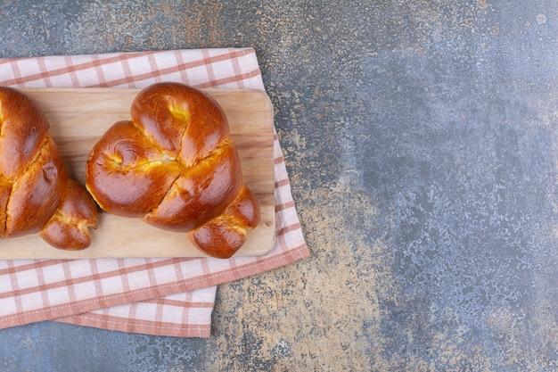 Panini a forma di cuore su una tavola sulla superficie di marmo