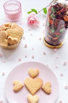 ピンクのプレートのバラとキャンドルのバレンタインデーのコンセプトにハート型のバタークッキー