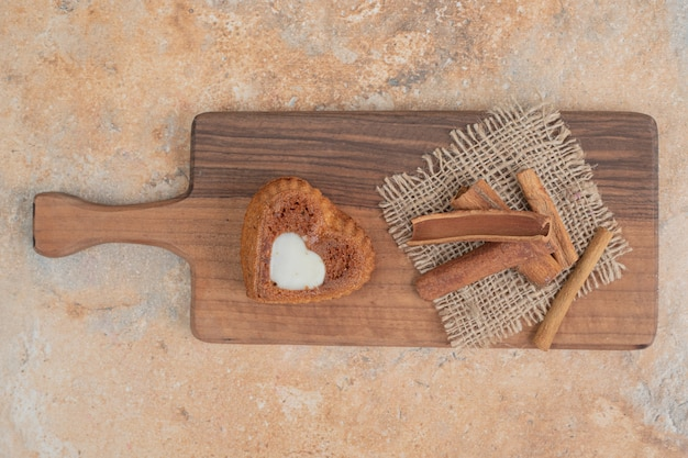 Heart shaped cake and cinnamon sticks on wooden board.