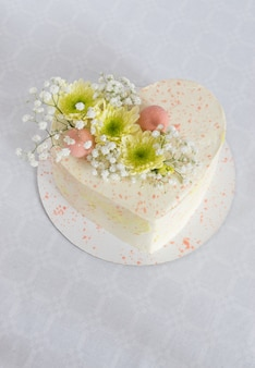 Heart-shaped cake decorated with fresh flowers on a white tablecloth