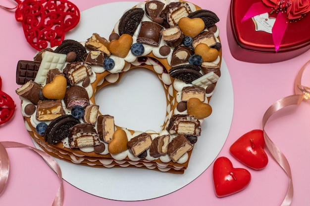 Heart-shaped cake on a pink background for valentine's day, birthday, march 8 and mother's day, closeup, top view
