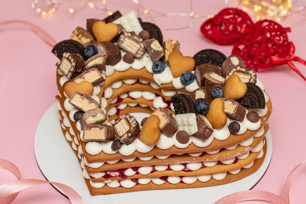 Heart-shaped cake on a pink background for valentine's day, birthday, march 8 and mother's day, closeup