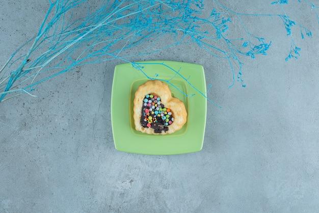 大理石の背景の大皿にチョコレートとキャンディーを詰めたハート型のケーキ。高品質の写真