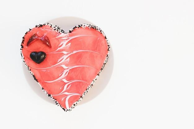 Торт в форме сердца с шоколадом и клубникой на тарелке