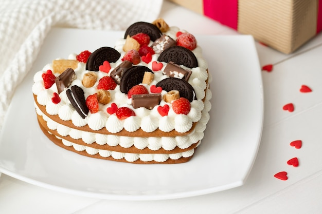 Торт в форме сердца с рикоттой и взбитыми сливками, украшенный шоколадом, вафлями, печеньем и клубникой.