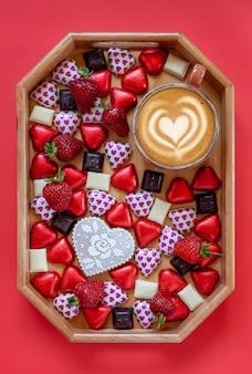 ハート型のキャンディー、ダークチョコレートとホワイトチョコレート、イチゴ、赤の背景の豚肉ボード上のラテコーヒーのカップ。クローズアップ、上面図。 Premium写真