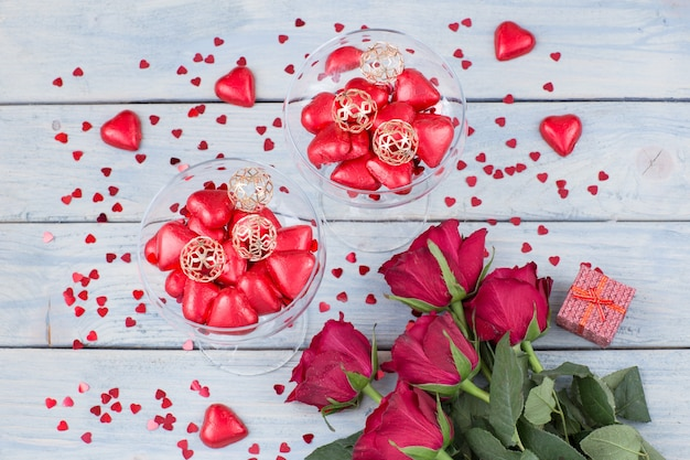 Heart shaped candies in glasses, gift and a bouquet of red roses