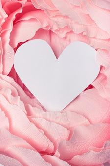 Heart shaped cardboard frame on spring pink paper background.