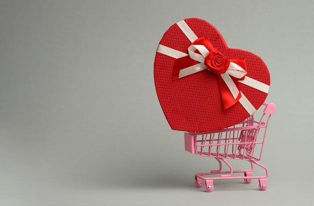 Heart shaped cardboard gift box in miniature metal trolley on gray surface. festive backdrop, surprise, seasonal sale