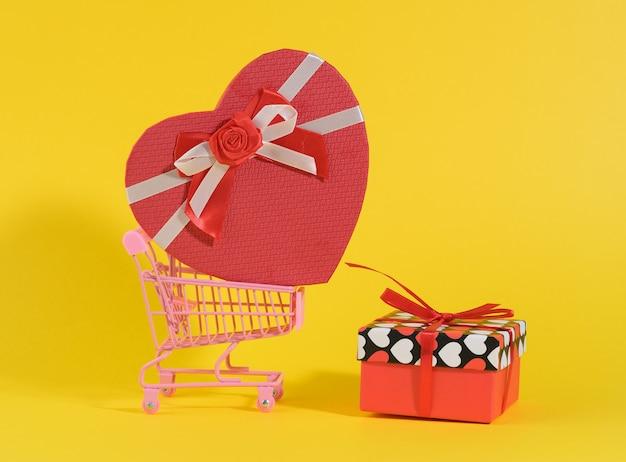 Heart shaped cardboard gift box in miniature metal trolley on yellow background. festive backdrop, surprise, seasonal sale