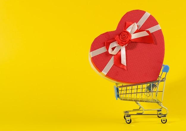 Heart shaped cardboard gift box in miniature metal trolley on yellow surface. festive backdrop, surprise, seasonal sale