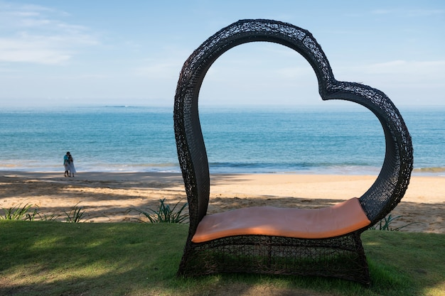 태국 팡아 해변에 흐릿한 커플이 있는 하트 모양의 의자.