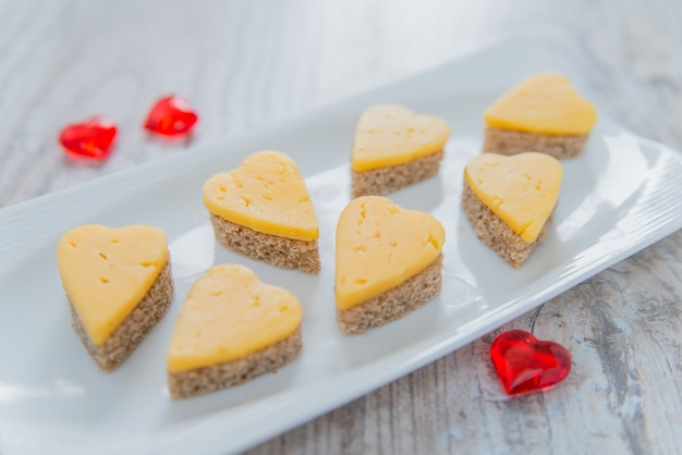 Heart shaped cheese sandwiches on a white plate