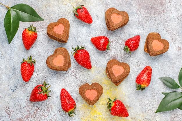 Шоколадно-клубничное печенье в форме сердца со свежей клубникой, вид сверху
