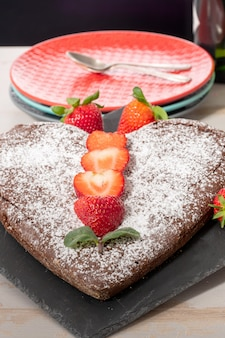 Heart shaped chocolate cake with strawberries