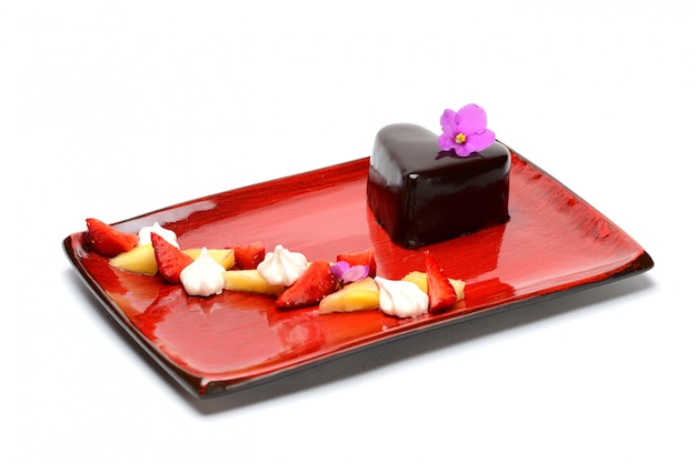 Heart-shaped chocolate dessert with strawberry and pineapple decor on a red plate