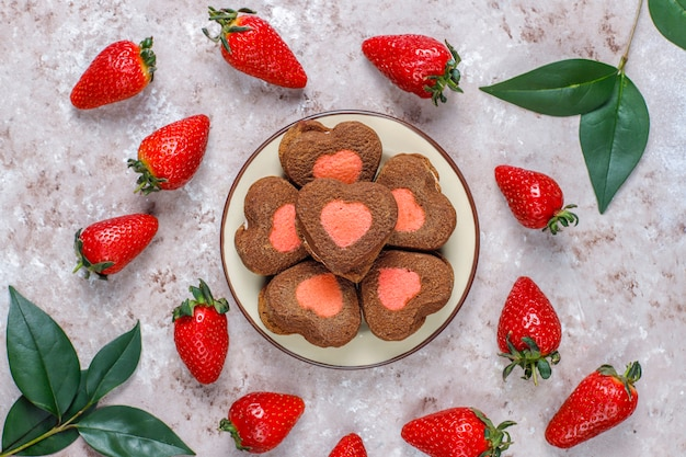 Heart shaped chocolate and strawberry cookies with fresh strawberries, top view