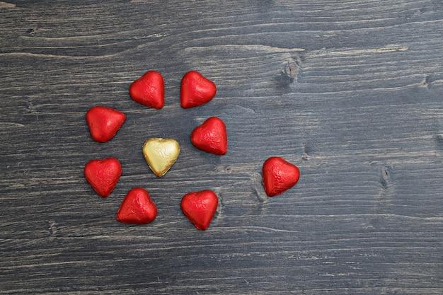 Конфеты в форме сердца в красной и золотой фольге на деревянном фоне